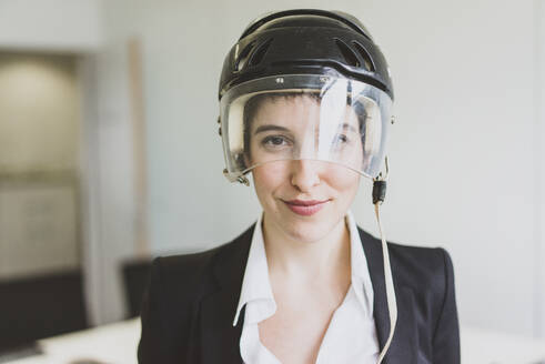 Portait of confident young businesswoman wearing ice hockey helmet in office - MOEF02634