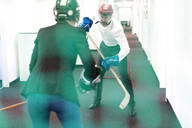 Businesswoman and businessman playing ice hockey in office - MOEF02637