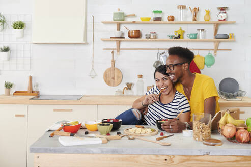 Multiethnic couple breakfasting together in the kitchen - IGGF01406