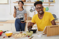 Multiethnic couple breakfasting together in the kitchen, using tablet and smartphone - IGGF01409