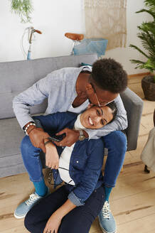 Multiethnic couple spending time together at living room, man kissing his girlfriend - IGGF01418