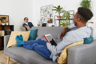 Multiethnic couple spending time together at living room, man holding tablet - IGGF01421