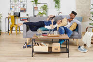 Multiethnic couple spending time together at living room - IGGF01424