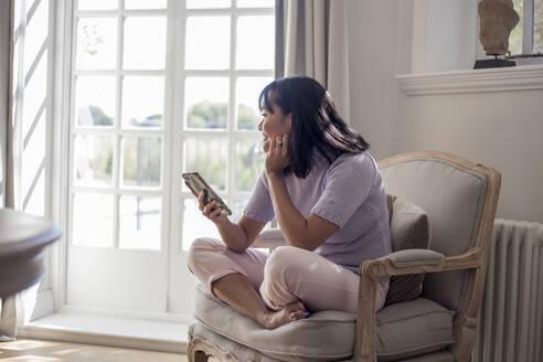 Woamn sitting on armchair, using smartphone - AJOF00051