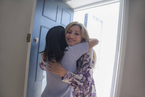 Two womengreeting each other with a hug at front door - AJOF00060