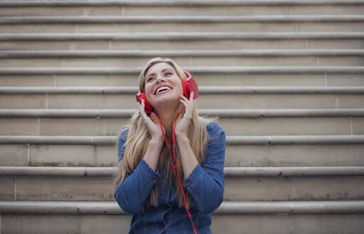 Portrait of smiling woman, listening to music on red headphones - AJOF00072
