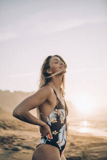 Young blond woman wearing swimsuit at the beach during sunrise - MTBF00109