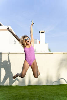 Portrait of screaming woman wearing pink swimsuit and mirrored sunglasses jumping in the air - ERRF01992