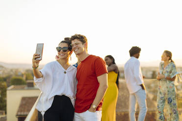 Young woman and man taking a selfie during a party in the evening - SODF00175