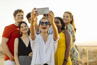 Group of happy multi-ethnic friends taking a selfie during a party in the evening - SODF00178