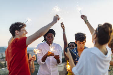 Group of happy multi-ethnic friends celebrating a party in the evening, holding sparklers - SODF00187