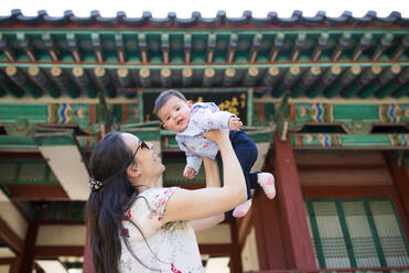 Mother and baby girl visiting pagoda in the Secret Garden, Changdeokgung, Seoul, South Korea - GEMF03260