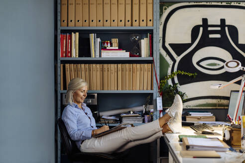 Mature woman working in architct's office, with feet up - SODF00211