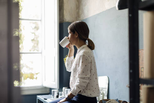 Woman drinking coffee in office kitchenet - SODF00229