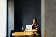 Woman using laptop, drinking cocktail - SODF00280