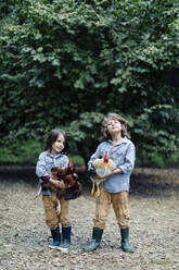 Two kids holding chickens on an organic farm - SODF00310