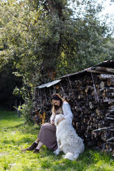 Pregnant woman with dog relaxing at stack of wood in garden - SODF00313