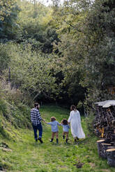 Rear view of family with two kids walking in the countryside - SODF00319