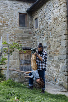 Father holding son upside down at a rustic farmhouse - SODF00325