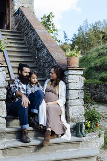 Family relaxing on stoop of a rustic house - SODF00328