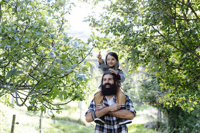 Happy father with kid on his shoulders in an orchard - SODF00334 - Sofie Delauw/Westend61