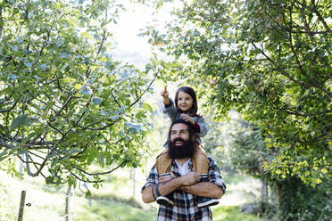 Happy father with kid on his shoulders in an orchard - SODF00334