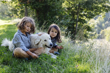 Two kids relaxing with dog on a meadow - SODF00337