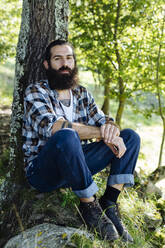 Portrait of man with beard sitting at tree trunk in the forest - SODF00349