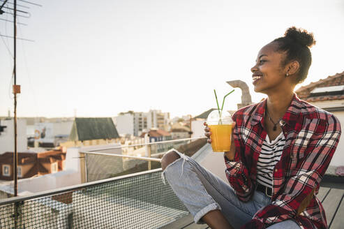 Happy young woman having a drink on rooftop at sunset - UUF19453