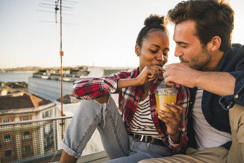 Young couple sharing a drink on rooftop in the evening - UUF19465