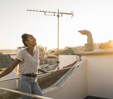 Laughing young woman standing on rooftop at sunset - UUF19483