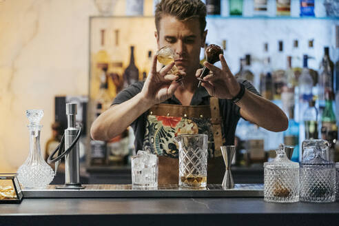 Bartender mixing cocktail in a bar - MTBF00133