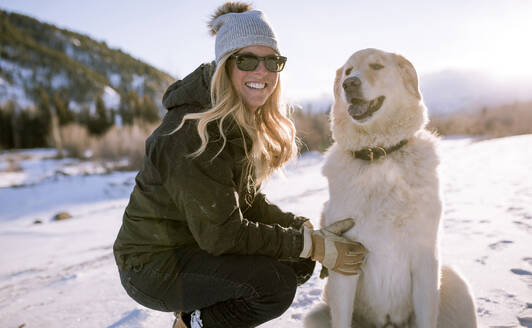Happy woman in sunglasses with dog on snowy field - CAVF68289