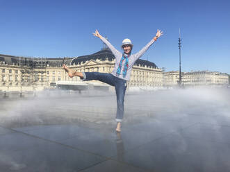 Woman having fun on Miroir d'eau, Bordeaux, France - GWF06250