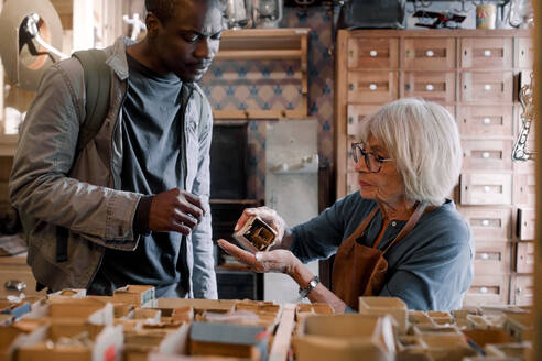 Senior saleswoman assisting male customer with nails at hardware store - MASF14048