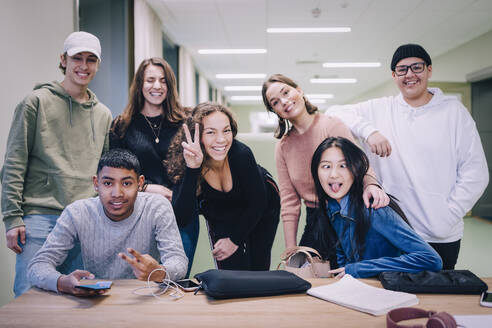 Portrait of teenage classmates making faces at desk in classroom - MASF14072