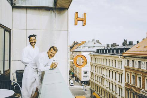 Smiling gay couple enjoying in hotel balcony - MASF14153