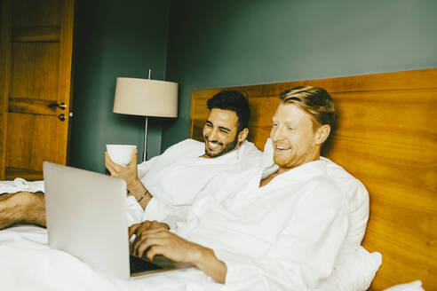 Smiling gay couple using laptop while leaning on bed in hotel room - MASF14156