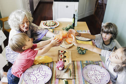 High angle view of grandmother and grandsons toasting juice at dining table - CAVF68360