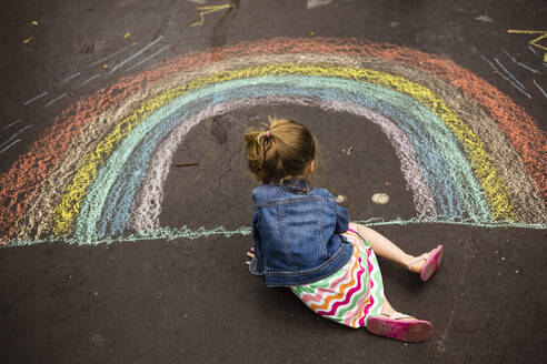 High angle view of girl drawing rainbow on asphalt - CAVF68459