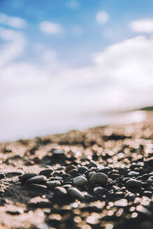 Surface level of pebbles at beach against sky - CAVF68480