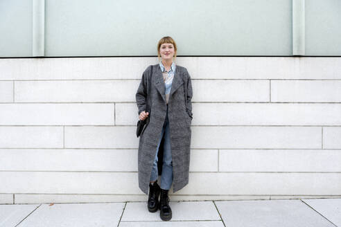 Portrait of strawberry blonde young woman wearing grey coat leaning against wall - FLLF00334