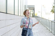 Portrait of young woman with smartphone freaking out - FLLF00343