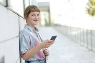 Portrait of strawberry blonde young woman with cell phone - FLLF00346
