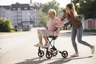 Granddaughter and her grandmother having fun with wheeled walker - UUF19511