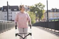 Senior woman with wheeled walker on footbridge - UUF19523