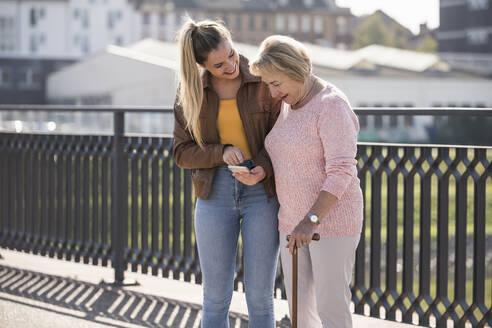 Granddaughter and her grandmother walking on footbridge and using smartphone - UUF19532