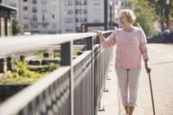 Senior woman walking on footbridge, using walking stick, looking away - UUF19535