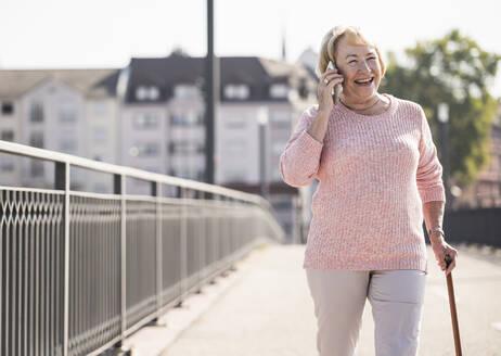 Senior woman walking on footbridge, using walking stick and phoning - UUF19538