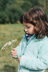 Portrait of little girl with wildflower in autumn - GEMF03274